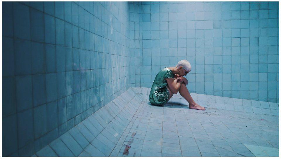 Julia Sophie Wagner sitzt in einem leeren Schwimmbecken, im Partyoutfit, verzweifelt und allein.