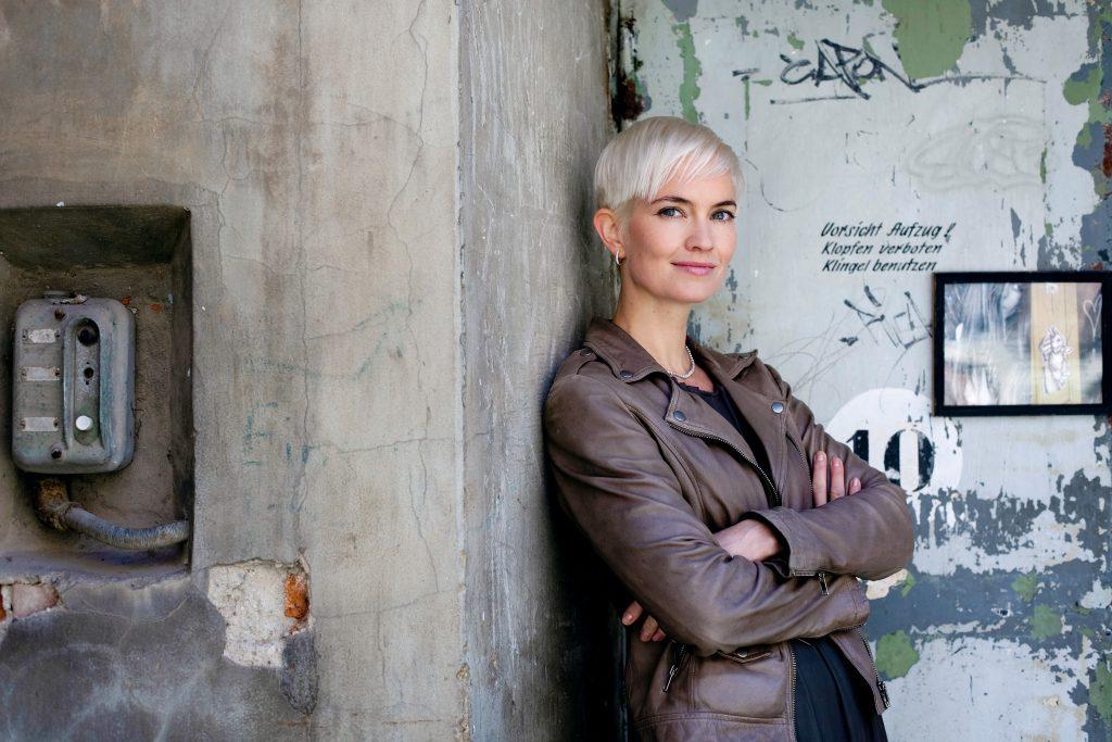 Julia Sophie Wagner angelehnt an eine alte Fabrikwand