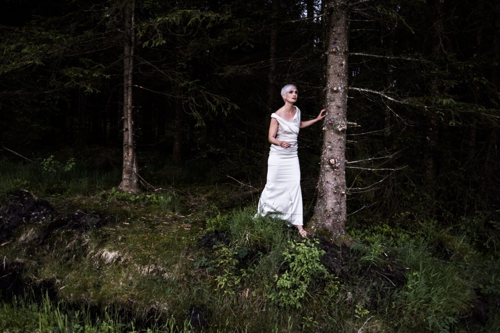 Julia Sophie Wagner in einem weißen Kleid barfuß in einem dunklen Wald stehend, mit suchendem Blick