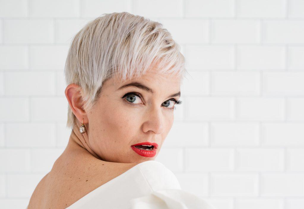 Die Sängerin Julia Sophie Wagner in einem weißen Kleid mit rot geschminkten Lippen. Portraitfoto mit Blick über die Schulter